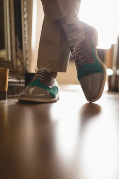 Man in casual shoes standing at home