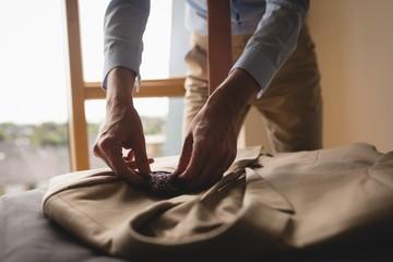 Man placing pocket square in blazer