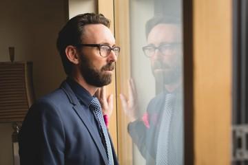 Man in full suit looking through window