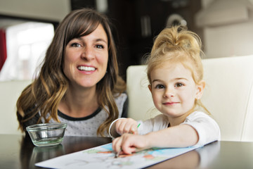 Mother and daughter painting together at home with paintbrushes and watercolors