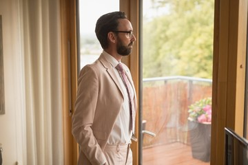 Man in full suit standing at home