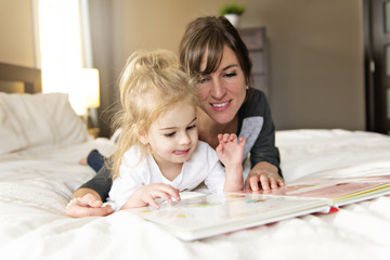 Cute little girl reading a book with her mother in the bedroom