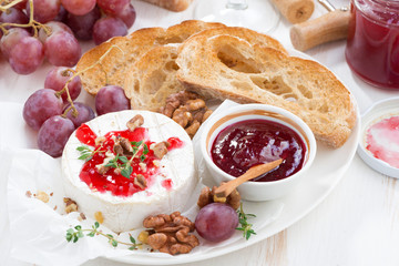 appetizers for wine - camembert with berry jam, toast and fruit on white table, top view