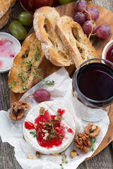 delicious appetizers for wine - camembert, berry jam, toast and fruit, close-up, top view