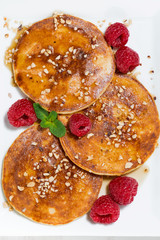 pancakes with raspberries on white plate, closeup