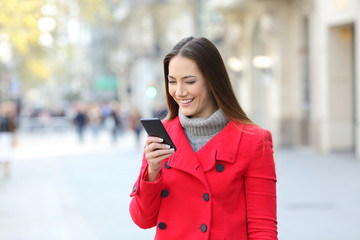 Lady using a smart phone on the street in winter