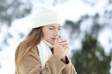Woman suffering cold outdoors in a snowy winter