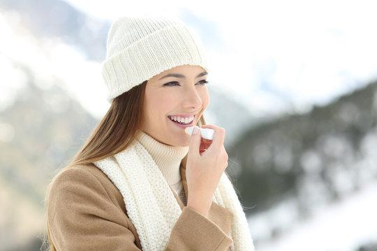 Woman applying lip balm in snowy winter