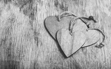 Stack of wooden hearts on an old board. Wooded valentines on a wooden background. Monochrome