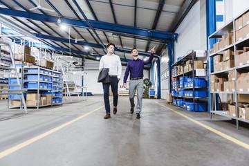 Two businessmen walking through shop floor, talking