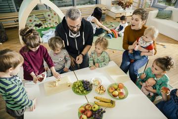 Group of children and teachers preparing fruit in kindergarten