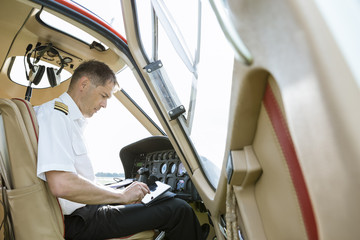 Pilot using tablet in cockpit of a helicopter
