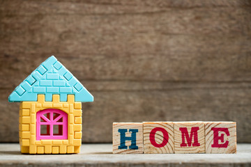 Puzzle model in home shape with block in home wording on wood background