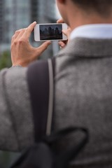 Businessman clicking photo with mobile phone