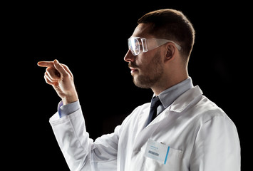 doctor or scientist in lab coat and safety glasses