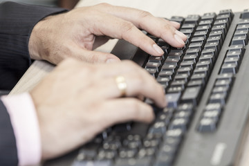 close-up hands of man on computer keyboard