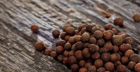 Fototapeta A heap of allspice, on wooden surface. Closeup view. obraz