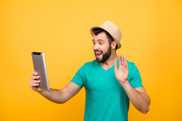 Hey how are you! Cute happy excited joyful cheerful guy in casual clothes is using digital tablet for communication with his relatives, isolated on vivid yellow background