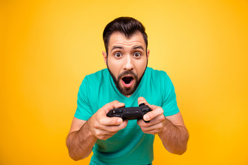I am number one in playing games! Close up portrait of funny joyful cheerful happy guy, he is rejoicing his victory with gamepad in hands, isolated on bright yellow background