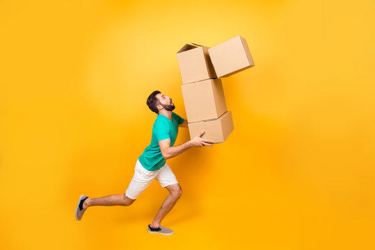Funny nervous man is carrying his stuff in boxes to the recently bought flat. He is holding cardboard boxes and one is falling down, isolated on yellow background