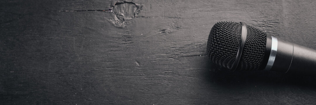 Microphone on a wooden black table. Studio. Top view. Free space for text. Copy space.