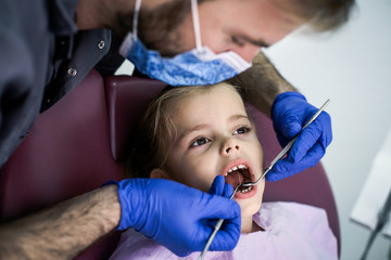 Young male dentist examining little girl. Close up.