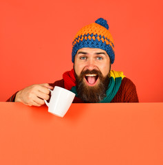 Man in warm hat holds white cup on orange background