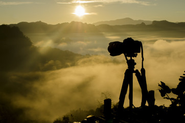 Silhouette of digital DSLR camera at beautiful view mountain point. Tourists or photographers are taking picture of mist and sunrise in morning, Chiang Mai, Thailand.