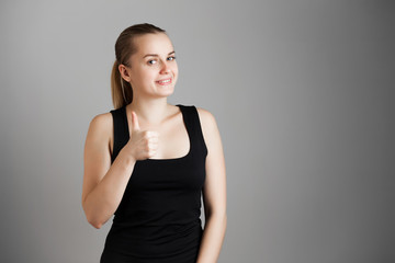 Portrait of young beautiful girl. Thumb up. Body language. Over grey background. Copy space.