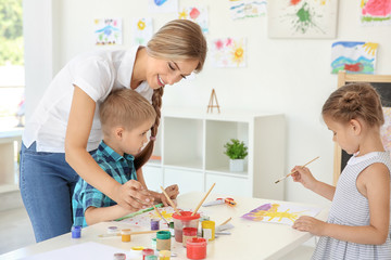 Children with teacher at painting lesson in classroom