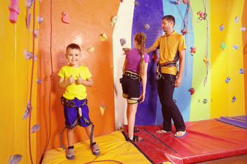 Little children with trainer in climbing gym
