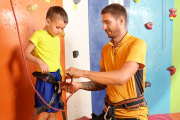 Trainer helping little boy to put on gear in climbing gym