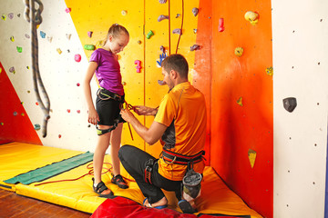 Trainer helping little girl to put on gear in climbing gym