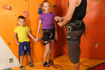 Little children with trainer in climbing gym