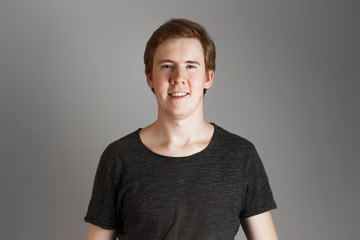 Portrait of young handsome hipster man with redheads, smiling laughing looking at camera. Over grey background.