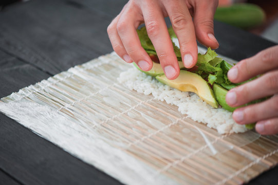 closeup of chef hands rolling up sushi
