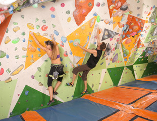 Young couple exercising in climbing gym