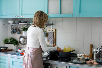 Back view of woman cooking spaghetti at home.