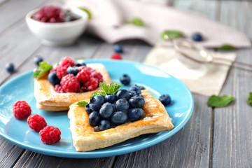 Plate with yummy berry puff pastry on wooden table