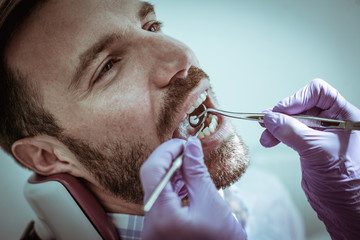 Men examining teeth at dentist office.
