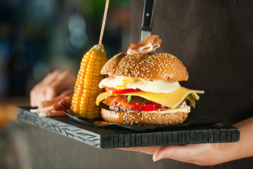 Woman holding wooden board with tasty burger, close up