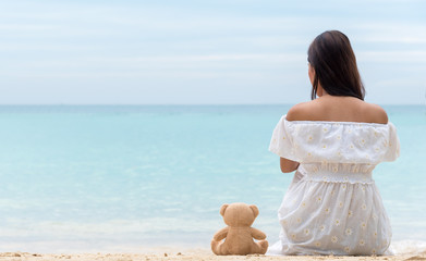Single women in white dress sitting alone with teddy bear is a friend by the sea, the girl who break heart  is lonely