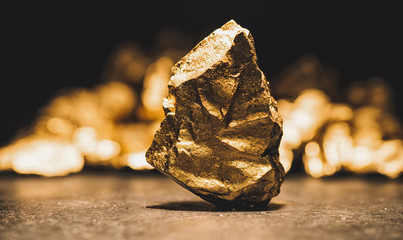 big gold nugget in front of a mound of gold -  finance concept
