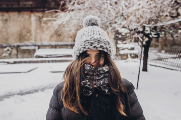 stylish hipster woman in knitted hat standing in snowy city street. beautiful fashionable girl in warm clothes in cold weather with wind. space for text