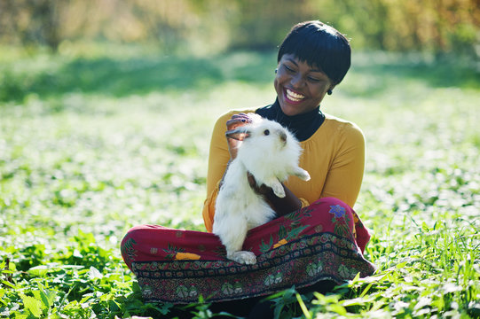 African american girl at yellow and red dress with white rabbit at hands.