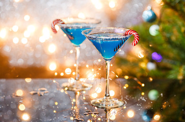 Christmas picture of two wine glasses with blue cocktail, caramel sticks and garland