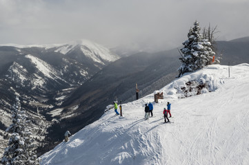 A group of skiers and snowboarders on the top of a trail.