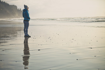 A young woman looks out at the Pacific Ocean from Neskowin Beach, Oregon.