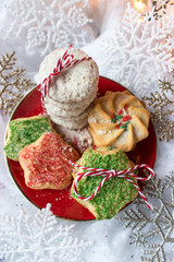 decorated Christmas cookies on red plate on snowy white background top view