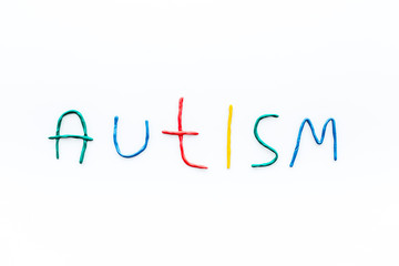 Childhood diseases. Word autism on white background top view copyspace